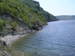 The Dniester River's shore near Bakota's rocky hills.