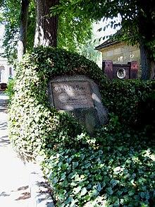 Das Grabmal von Jean Paul und seinem Sohn auf dem Bayreuther Stadtfriedhof: Der Gedenkstein ist ein efeuüberwucherter Findling. (Quelle: Wikimedia)