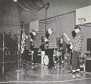 Brian Wilson - Wilson (second-left) performing with the Beach Boys in Pendleton outfits at a local high school in late 1962