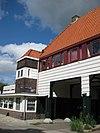 foto van Poortgebouw met twee winkels met bovenwoningen, met veel hout zoals de zware kolommen in poort, bouwstijl Amsterdamse School, ligging aan Purmerweg centraal deel van Tuindorp Nieuwendam