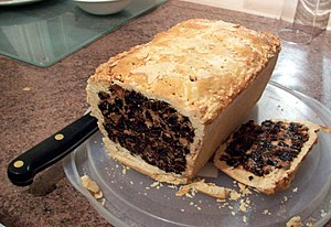 A black bun cut open, showing the fruit cake i...