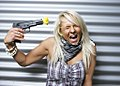 Blode woman with a plastic gun with a yellow flower on the barrel.jpg