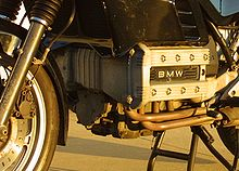 Closeup picture of BMW K100 engine. Also shows some black bodywork, forks and a front brake calliper