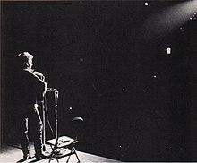 Een spot schijnt op Dylan als HIJ Voert het podium.