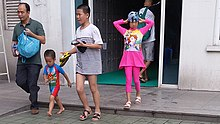 An adult walks with three children. The children are dressed to go swimming.