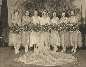 Bridesmaid - The bride (center) with her maid of honor (third from left) and bridesmaids.  The maid of honor can be distinguished by her dress, which differs somewhat from that of the other bridesmaids, as well as by her position in the traditional place of honor at the immediate right of the principal party.  From 1929, in Minnesota, USA.
