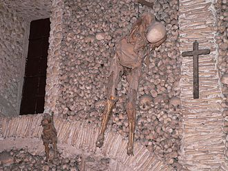 Capela dos Ossos - Image of two skeletons hanging from ropes.