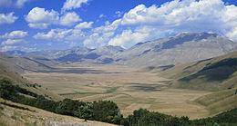 Vista dell'Altopiano di Castelluccio: in fondo a sinistra si scorge il paese in cima ad una collina. Sulla destra, il Monte Vettore.