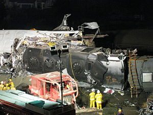 Rescue workers in front of the Metrolink locomotive lying on its side after penetrating the lead passenger car (left)