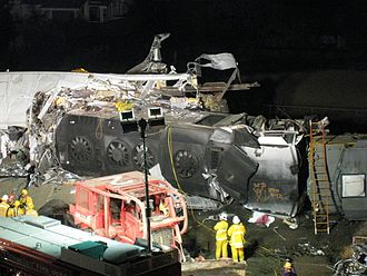 2008 Chatsworth train collision - Rescue workers in front of the Metrolink locomotive lying on its side after penetrating the lead passenger car (left)