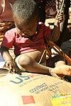 Child on food aid bag (8329688651).jpg