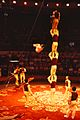 Chinese acrobat in midair being watched by other acrobats.jpg