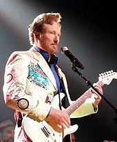 A man in a white jacket and blue shirt plays a white guitar.