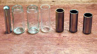 "Slide guitar - A collection of various guitar slides.  On the left is a ""steel"" used in lap playing.  The next two are Coricidin medicine bottles from the late 1960s; followed by a polycarbonate tube and three metal tubes"