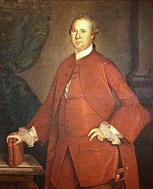 An eighteenth century painting shows a middle aged man dressed in red clothing leaning on two books that are resting on a table, with a Roman-style column in the background