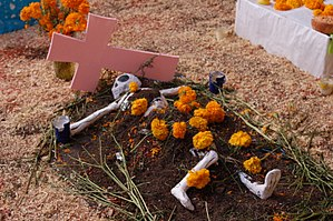 Tomb with tagetes flowers and a skull on it at...