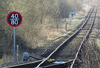Cambrian Line - An example of a metric speed limit sign, west of Machynlleth, installed as part of the ERTMS upgrade. It shows a differential limit with different speeds for passenger and freight trains.