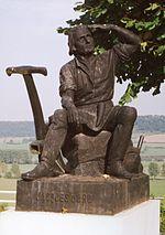 Jacques d'Arc et Isabelle Rommée, parents de Jeanne (vue d'artiste par l'Union internationale artistique de Vaucouleurs). Statues érigées en 1911 sur le parvis de la basilique du Bois-Chenu à Domrémy-la-Pucelle (Vosges)[11],[12].