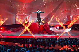 A man dressed in a black dressed performing on a stage in front of a red background and behind X-shaped pyrotechnics.
