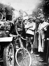 On the left a classic automobile, and a group of men standing, one of them holding a bicycle.