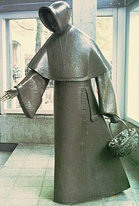 A stylised metal statue of a hooded woman holding a basket.