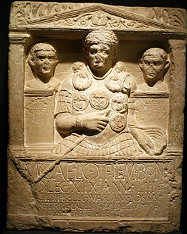 A stone carving, the border resembling a Greco-Roman building, displaying three busts, slightly damaged, the centremost being that of Marcus Caelius, wearing armour, a cape and holding a dagger in his right hand. Below the carving is a Latin inscription.
