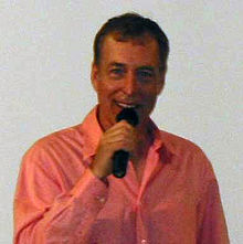 A man with short dark hair in a pink shirt, speaking into a microphone in his right hand.