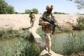 Foot patrol crosses a foot bridge in Marjah, Afghanistan.jpg