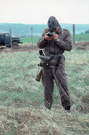Border Troops of the German Democratic Republic - East German Grenzaufklärungszug (GAK) border trooper taking a photograph of US Army activities across the inner German border.