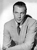 Black and white photo of Gary Cooper in 1936—a handsome white man, light-eyed with hair combed back, wearing a light-colored suit and around 30 years of age.