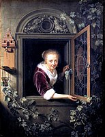 En jente i et vindu med en haug med druer