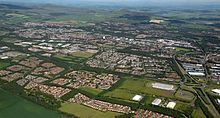 Aerial image of southern Glenrothes (looking northwest) showing housing estates, industrial areas, road networks and green spaces and landscaping in the town. The Lomond Hills can be seen to the north