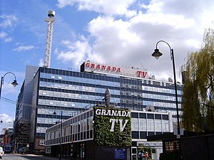 ITV Granada - Granada Studios with the red logo and lattice broadcasting tower on the roof – both of which have been removed in recent years.