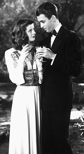 Hepburn and a smartly dressed man standing at night by a pool. She is holding a glass of champagne and they are looking at each other flirtatiously.