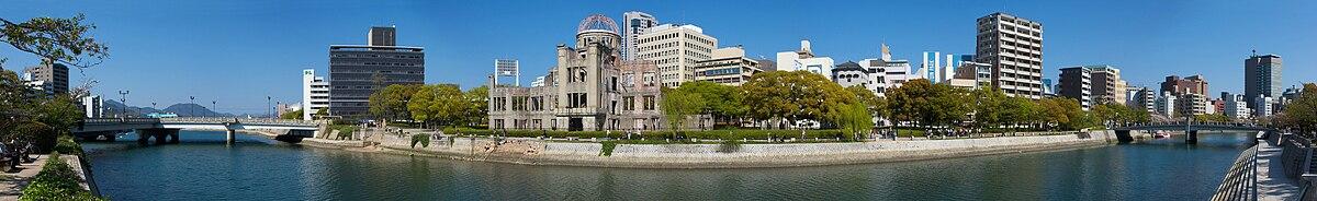 Vista del Monumento de la Paz de Hiroshima. La Cúpula Genbaku, la cual permaneció en pie después del bombardeo, se ve claramente al centro de la imagen. El blanco original de la bomba era el puente Aioi, a la izquierda en la vista panorámica.