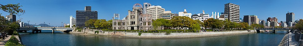 "Panoramic view of Hiroshima Peace Memorial Park. The Genbaku Dome can be seen in the center left of the image. The original target for the bomb was the ""T""-shaped Aioi Bridge seen in the left of the image."