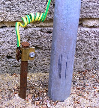 Ground (electricity) - A typical earthing electrode (left of gray pipe), consisting of a conductive rod driven into the ground, at a home in Australia. Most electrical codes specify that the insulation on protective earthing conductors must be a distinctive color (or color combination) not used for any other purpose.