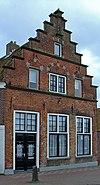 foto van Huis met trapgevel met zandstenen afdekkingen en waterlijsten, toppilaster en gerestaureerd bovenstuk