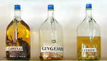 "three bottles of liquid in various colors on a shelf, labeled ""cinnamon,"" ""ginger"" and ""lemon"""
