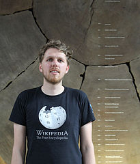 Photo shows John, wearing a black Wikipedia t-shirt, in front of a cross section of a giant sequoia, one of the largest trees in the world