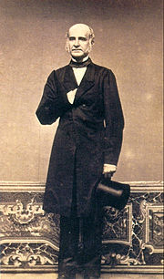 A full-length photograph of a balding man with long sideburns, dressed in a formal frock coat and black tie and holding a black top hat in his left hand at his side