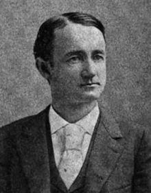 A man with dark hair wearing a black jacket, white shirt, and light tie with a large knot