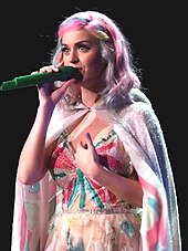 Katy Perry performing in a pink cloak, during the Prismatic World Tour