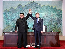 Kim and Moon raise clasped hands