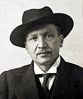 A picture of Kullervo Manner, chairman of the Finnish People's Delegation and last commander-in-chief of the Reds, looking straight at the camera with a suit and a hat on.