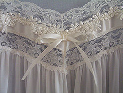 Lace appliqué and bow at the bust-line of a nightgown.