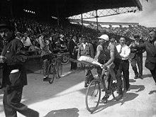 Photographie en noir et blanc d'un cycliste accomplissant un tour d'honneur, un bouquet à la main, devant une foule enthousiaste.