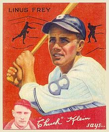 "A baseball card showing a man wearing a white baseball uniform with a blue ""B"" on the chest and a blue cap holds a bat above his right shoulder."