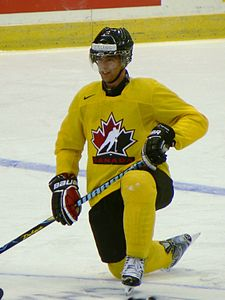 An ice hockey player wearing full equipment is kneeling on the ice with a smirk on his face. His uniform clearly indicates he is part of a national team, and his surname is stickered on the front of his helmet