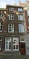 foto van Huis met lijstgevel, voorzien van vensters in Naamse steen en horizontale reliefbanden.